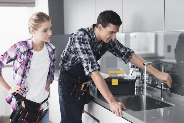 Mężczyzna i kobieta hydraulik naprawiają baterię kuchenną.