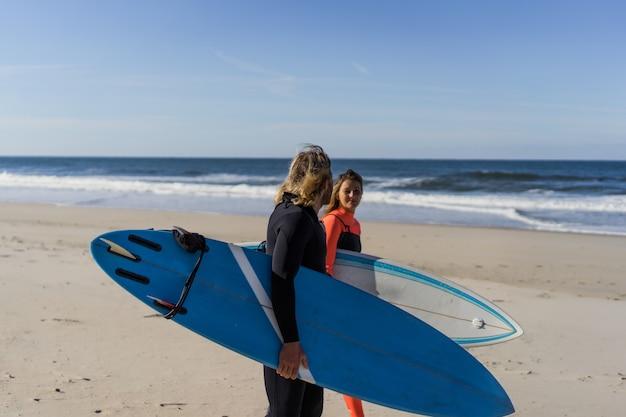 Mężczyzna i kobieta idą do oceanu z desek surfingowych. mężczyzna i dziewczyna surfują