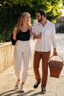 Mężczyzna i kobieta idą do parku na piknik