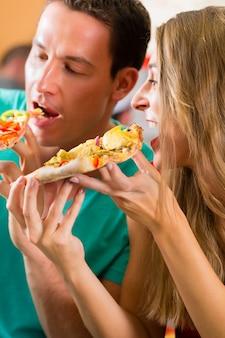 Mężczyzna i kobieta je pizzę