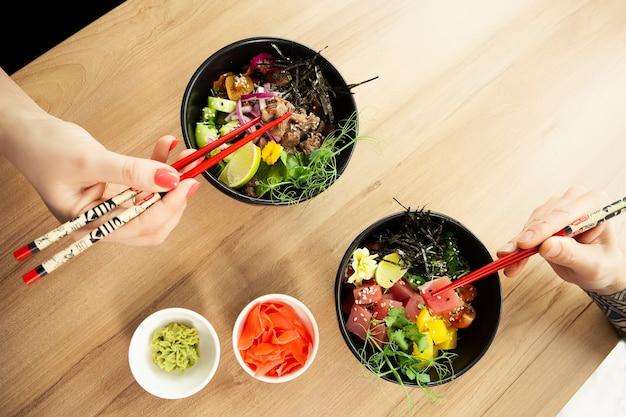 Mężczyzna i kobieta jedzą sałatkę poke z pałeczkami dab sałatkę z tuńczyka w misce ludzie w restauracji