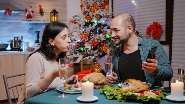 Mężczyzna i kobieta jedzą świąteczny obiad, patrząc na smartfona