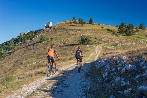 Mężczyzna i kobieta jedzie mtb do ruin zamku na szczycie góry w rocca calascio, włoski cel podróży, park narodowy gran sasso, abruzja, włochy. czyste błękitne niebo