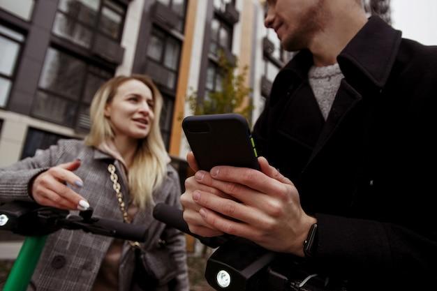 Mężczyzna i kobieta jeżdżą po mieście skuterami elektrycznymi. omawiają nową aplikację na smartfony do wypożyczania e-skuterów. skoncentruj się na telefonie w rękach mężczyzny. zamazani ludzie i bloki mieszkalne.