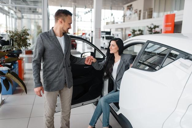 Mężczyzna i kobieta kupują nowy samochód w salonie.