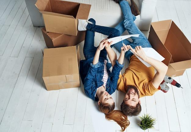 Mężczyzna i kobieta leżą na podłodze obok pudeł remontujących poruszający się pokój. zdjęcie wysokiej jakości