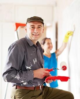 Mężczyzna i kobieta maluje ścianę