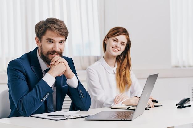 Mężczyzna i kobieta menedżerowie rozmawiają przy stole przed laptopem specjalistów technologii. zdjęcie wysokiej jakości