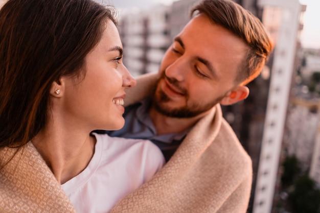 Mężczyzna i kobieta na balkonie o zachodzie słońca w mieście