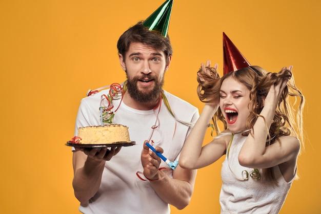 Mężczyzna i kobieta na urodziny z babeczką i świecą w świątecznej czapce baw się dobrze i razem świętuj wakacje, szczęśliwa para