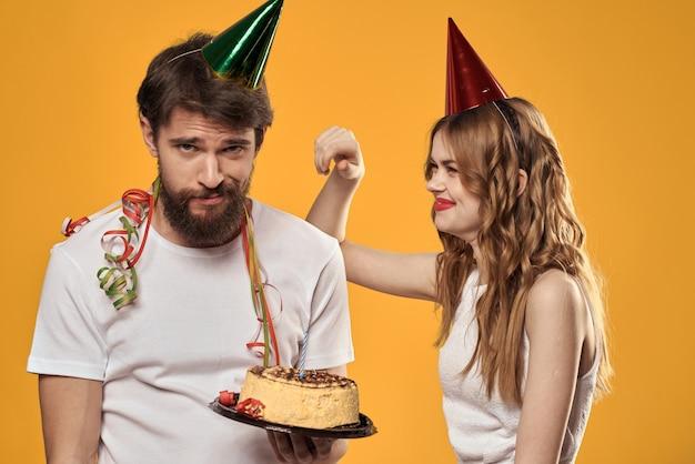 Mężczyzna i kobieta na urodziny z ciastem i świeczką w świątecznych czapkach dobrze się bawią