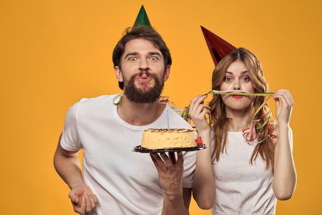 Mężczyzna i kobieta na urodziny z tortem i świeczką w świątecznych czapkach