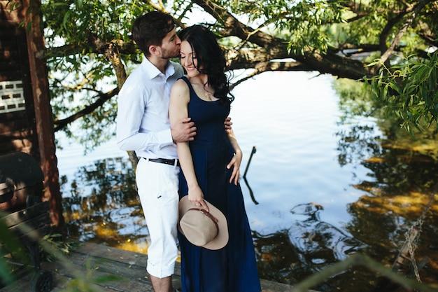 Mężczyzna i kobieta nad jeziorem spędzają czas w swoich ramionach