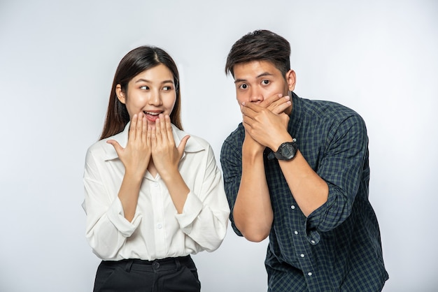 Mężczyzna i kobieta nosili koszule i zakrywali usta rękami w szoku