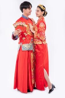 Mężczyzna i kobieta noszą cheongsam, ciesząc się, że otrzymują pieniądze w prezencie i gotówkę