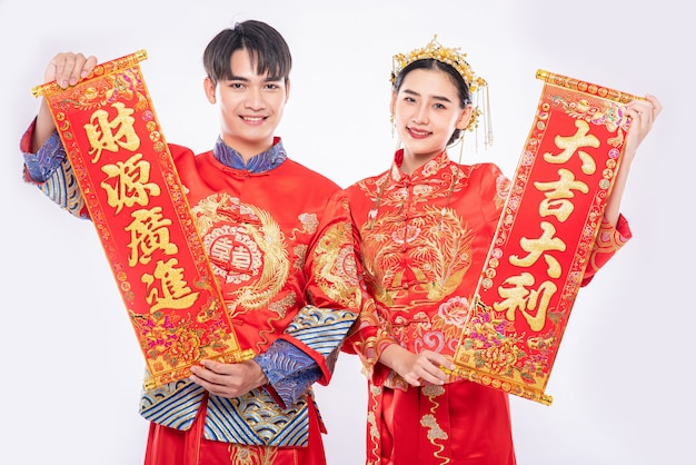 Mężczyzna i kobieta noszą garnitur cheongsam świętują chiński nowy rok z chińską kartką z życzeniami