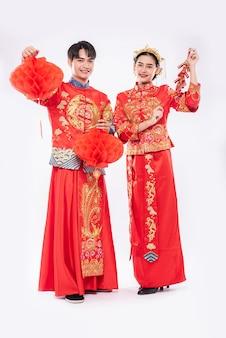 Mężczyzna i kobieta noszą garnitur cheongsam świętując chiński nowy rok czerwoną lampą i petardą