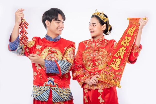 Mężczyzna i kobieta noszą kombinezon cheongsam świętują chiński nowy rok z chińską kartką z życzeniami i petardą razem