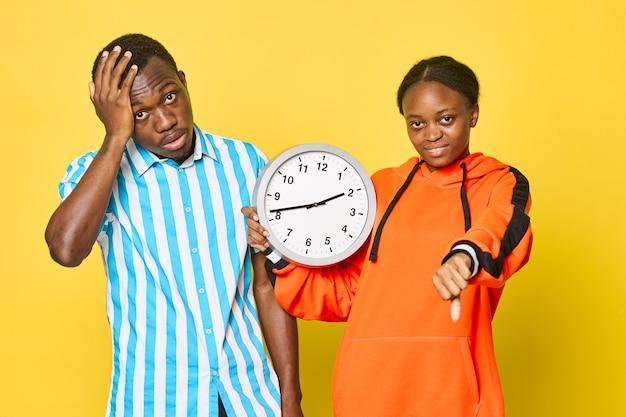 Mężczyzna i kobieta o afrykańskim wyglądzie z okrągłym zegarem