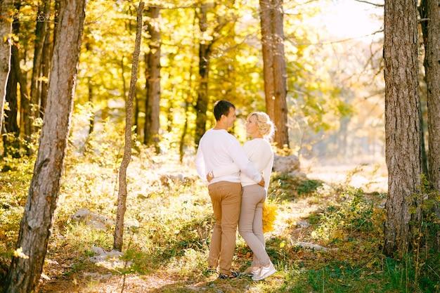 Mężczyzna i kobieta obejmują widok z tyłu lasu jesienią