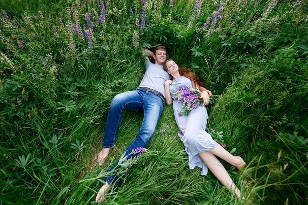Mężczyzna i kobieta obejmującego leżącego w trawie