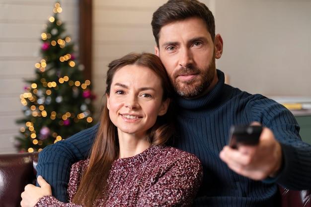 Mężczyzna i kobieta oglądają telewizję w boże narodzenie