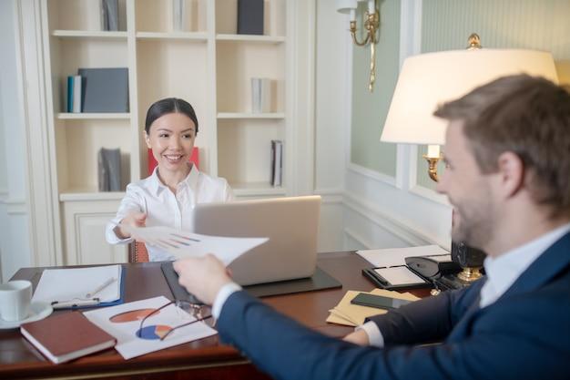 Mężczyzna i kobieta omawiający wskaźniki kpi swojej firmy