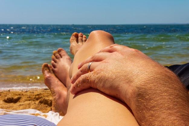 Mężczyzna i kobieta opalają się na morskiej plaży, dłoń mężczyzny ze złotą obrączką leży na biodrze kobiety na niebieskim tle morza