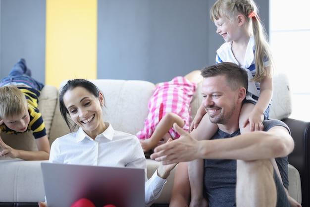 Mężczyzna i kobieta oraz ich dzieci uśmiechają się i śmieją, siedząc na podłodze i patrząc na laptopa.