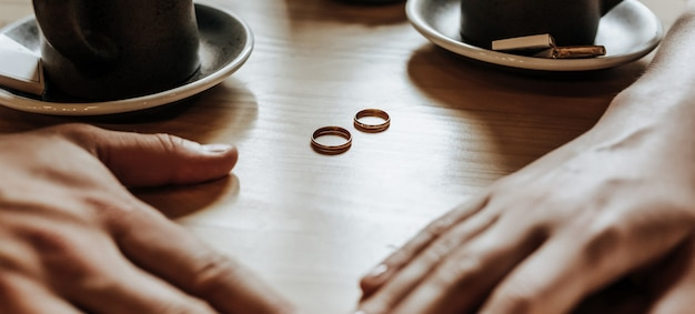 Mężczyzna i kobieta para nowożeńców trzymają się za ręce z pierścieniami w kawiarni przy filiżance kawy. państwo młodzi są zakochani