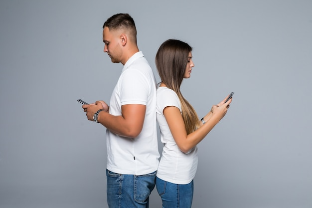 Mężczyzna i kobieta para stojących z marki telefonów komórkowych w ich rękach na białym tle na szarym tle