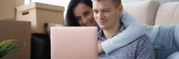 Mężczyzna i kobieta patrzą na laptopa obok pudełek. znalezienie noclegu dla podróżników