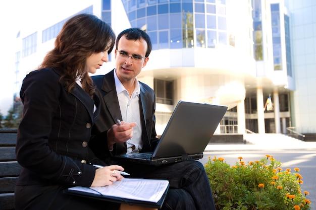 Mężczyzna i kobieta, patrząc na ekran laptopa i siedząc na ławce przed budynkiem biurowym przy słonecznej pogodzie