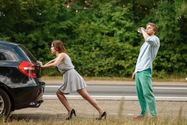 Mężczyzna i kobieta pchają zepsuty samochód na drodze, awaria
