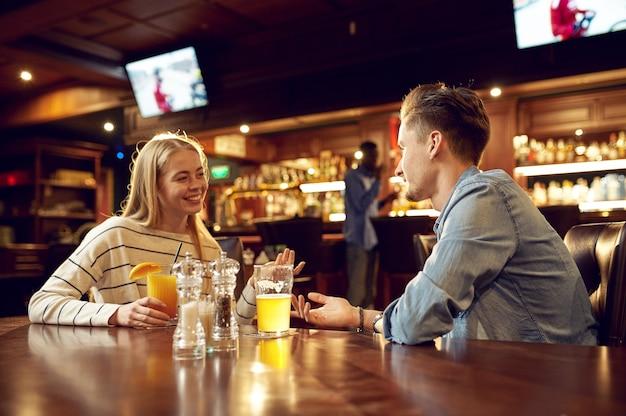 Mężczyzna i kobieta piją alkohol i rozmawiają przy stole w barze. grupa ludzi odpoczywa w pubie, nocnym stylu życia, przyjaźni, uroczystościach