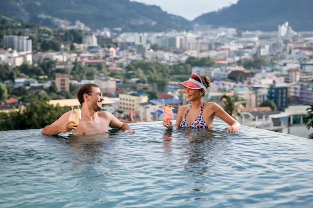 Mężczyzna i kobieta piją koktajle w basenie bez krawędzi