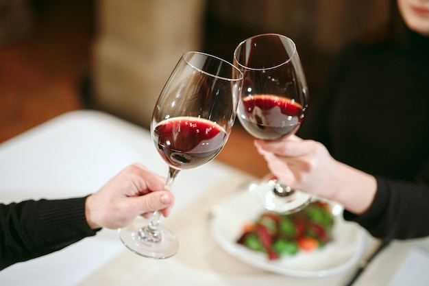 Mężczyzna i kobieta pije czerwone wino. na zdjęciu zbliżenie dłoni w okularach.