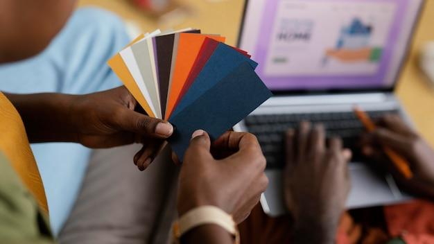 Mężczyzna i kobieta planują remont domu przy użyciu palety kolorów i laptopa