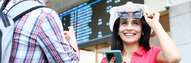 Mężczyzna i kobieta pod tablicą informacyjną ze smartfonem