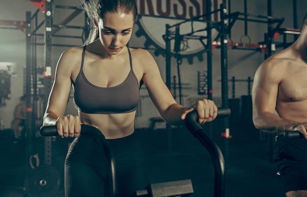 Mężczyzna i kobieta podczas ćwiczeń w siłowni fitness.