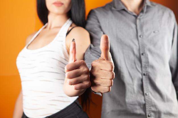 Mężczyzna i kobieta pokazują kciuki do góry na pomarańczowym tle