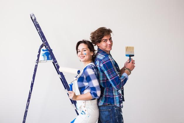 Mężczyzna i kobieta pokryte farbą w nowym mieszkaniu.