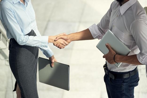 Mężczyzna i kobieta pozdrowienia siebie drżenie rąk w biurze