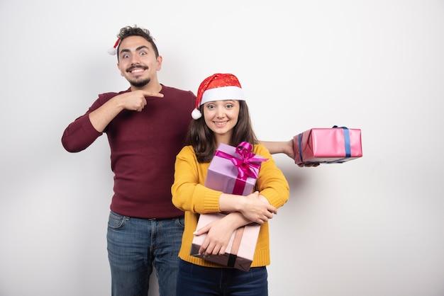 Mężczyzna i kobieta pozuje z prezentami świątecznymi.