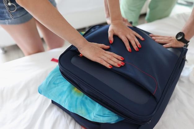 Mężczyzna i kobieta próbują zamknąć pełną walizkę ze zbliżeniem rzeczy
