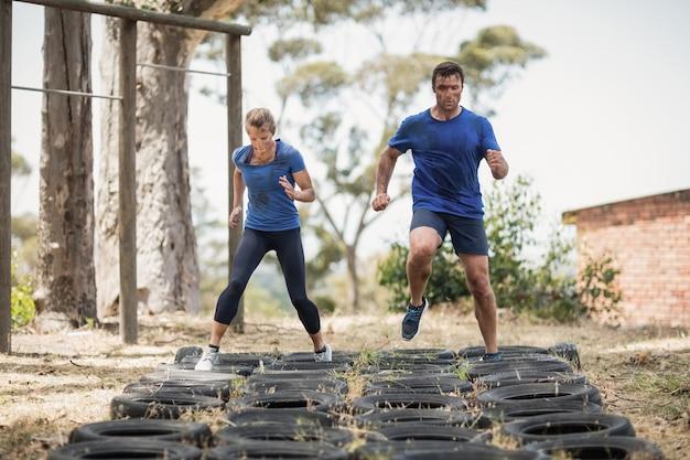 Mężczyzna i kobieta przejeżdżają przez oponę podczas toru przeszkód w obozie treningowym