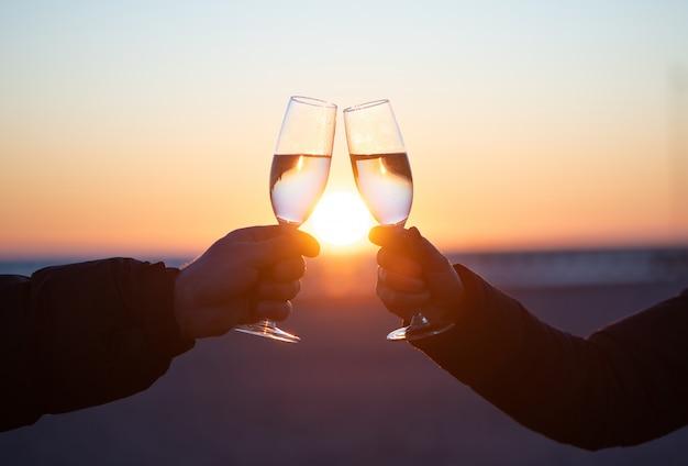 Mężczyzna i kobieta przy lampce wina o zachodzie słońca