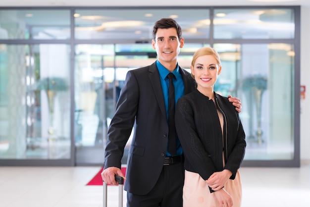 Mężczyzna i kobieta przybywających do holu hotelu z walizką
