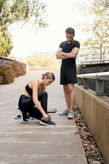 Mężczyzna i kobieta przygotowuje się do ćwiczeń razem na świeżym powietrzu