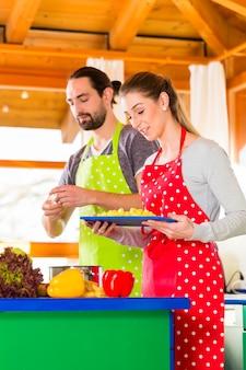 Mężczyzna i kobieta przygotowuje zdrowy posiłek w domowej kuchni w domu